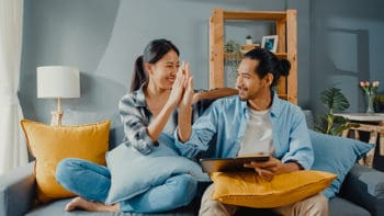 Happy asian young attractive couple man and woman sit on couch u